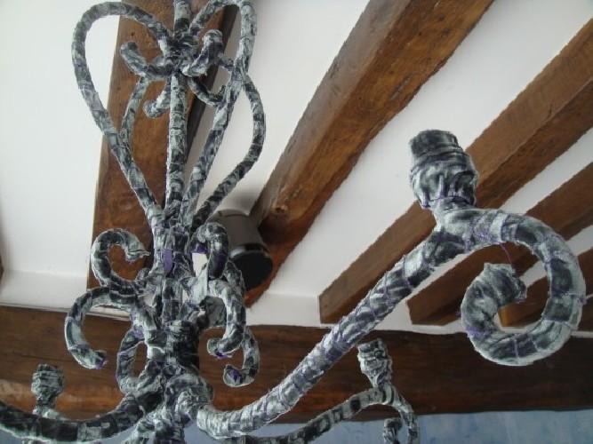 Des habits de velours baroque pour ce lustre 4 branches en fer forgé